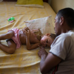 Fitia's father comforts her during our visit to their home to explain that we could bring her to the ship for surgery.
