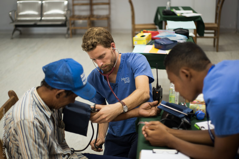 ©2015 Mercy Ships, Photo Credit Josh Callow - Nate CLAUS (USA) examines a potential patient at a screening in Mahajanga